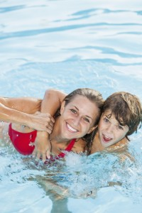 Mother (30s) and son (9 years) having fun in swimming pool.
